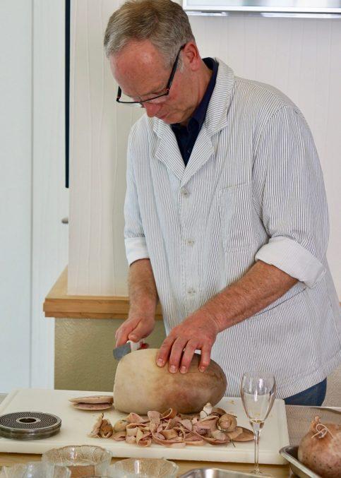 A butcher in striped jacket slicing a Saumagen