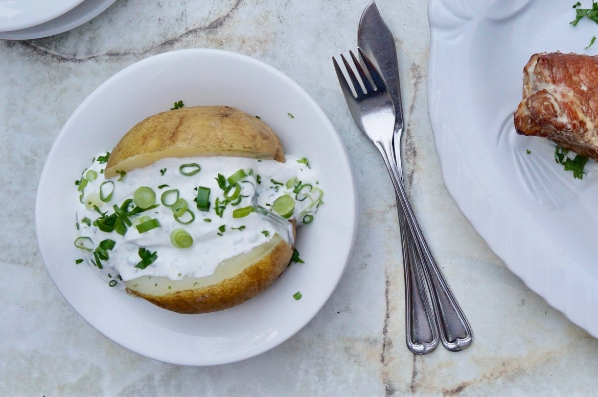 A baked potato filled with quark and chopped spring onions on a white plate and marble table