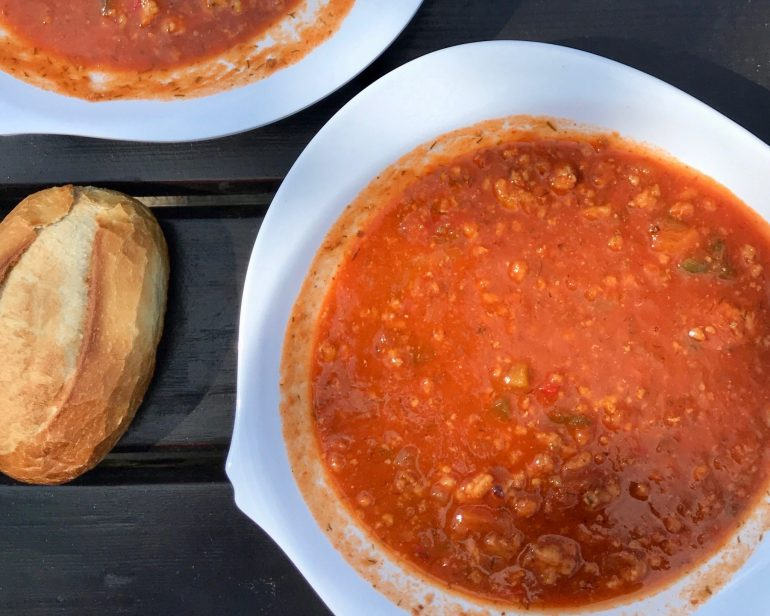 Flatlay of a white, fish-shaped bowl of reddish-brown Soljanka soup with a crusty white bread roll on a wooden table