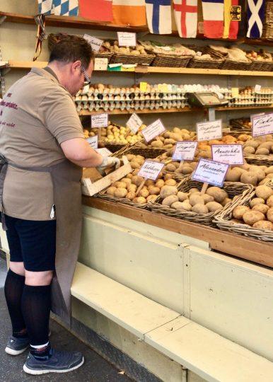 Man putting potatoes into crates at a potato stall at a farmers market