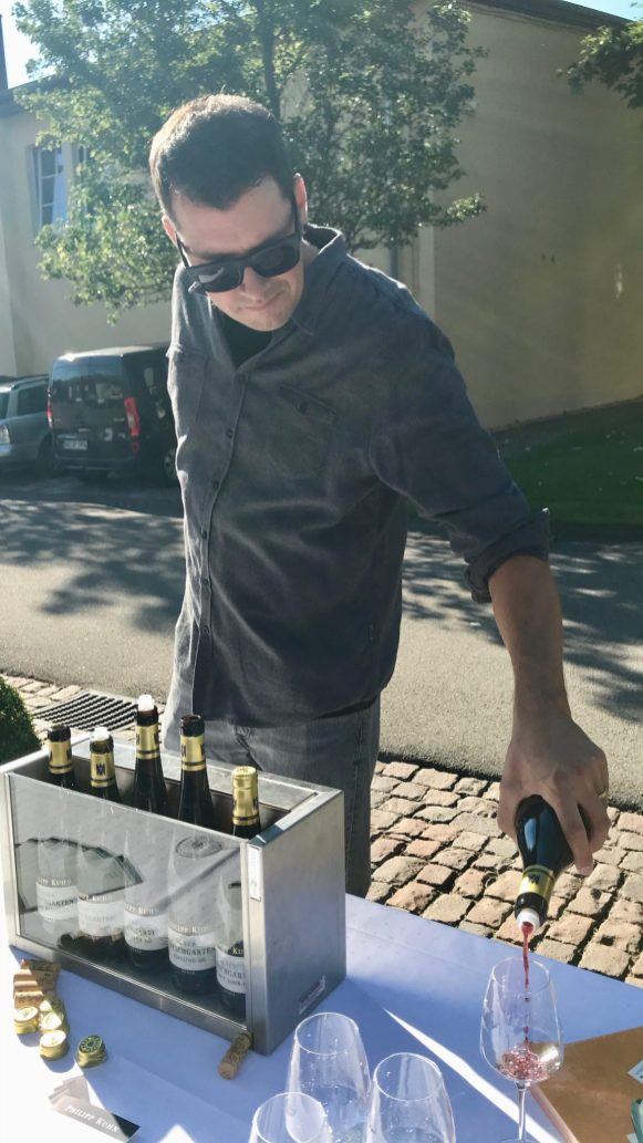 Man pouring wine outside at a table