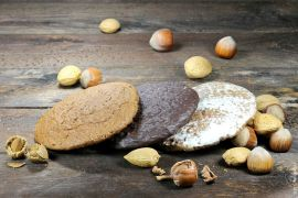Three Nürnberger Elisenlebkuchen on a wooden table with some nuts