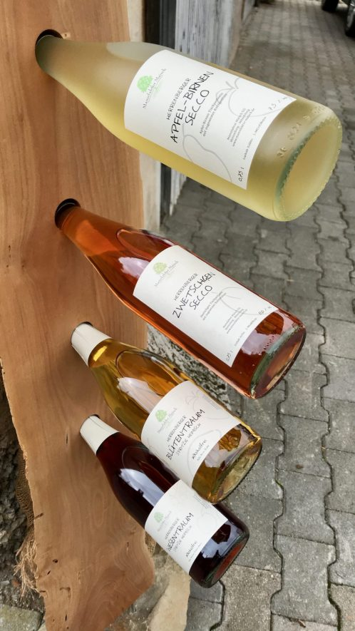 Four bottles of fruit secco in a wooden stand