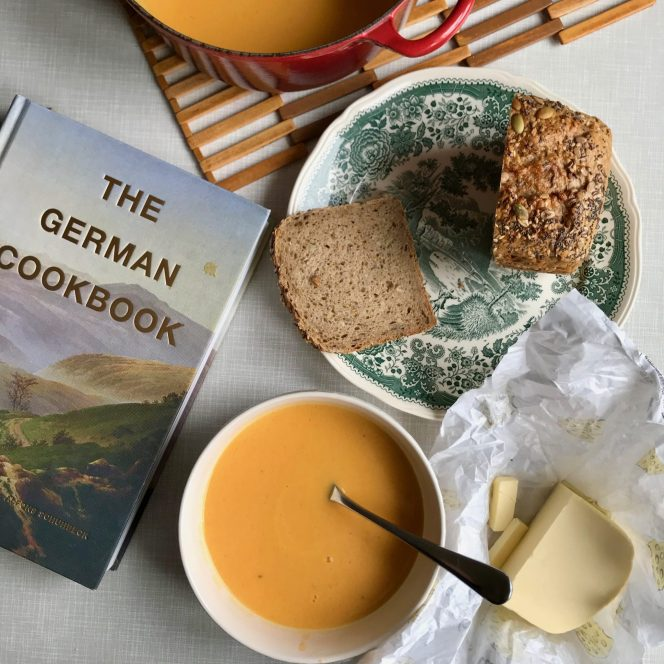 A flatlay of a bowl of pumpkin soup, some sliced bread on a green and white plate, a pat of butter and a large cookbook