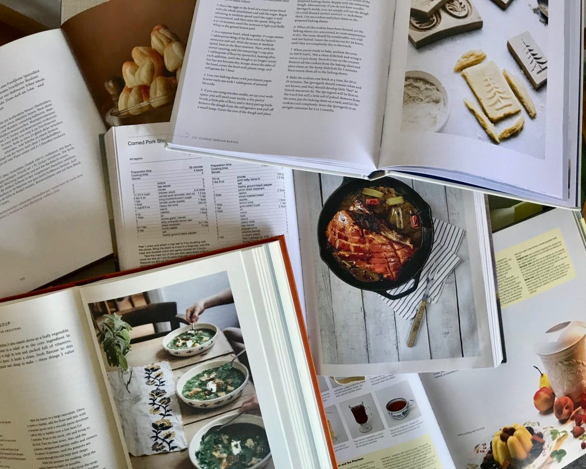 Five German cookbooks lying open on top of each other