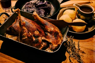 A whole roast goose in a roasting tray with dumplings and red cabbage on the side