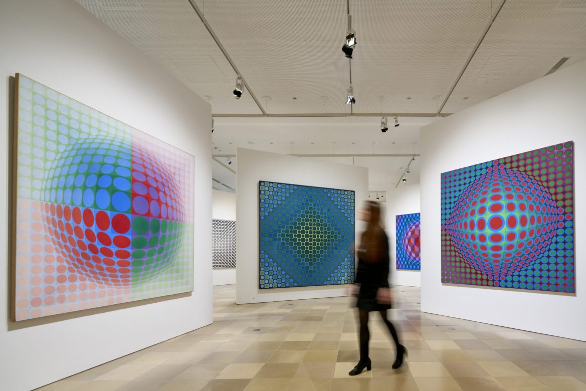 A white museum gallery with brightly coloured paintings by Victor Vasarely