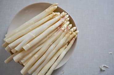 A plate of peeled white asparagus on a beige plate on a grey table, from above