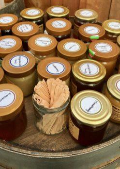 Tester jars of honey on a barrel