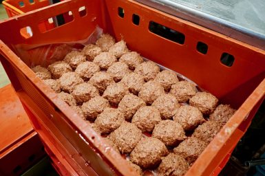 Raw Leberknödel lined up in a crate