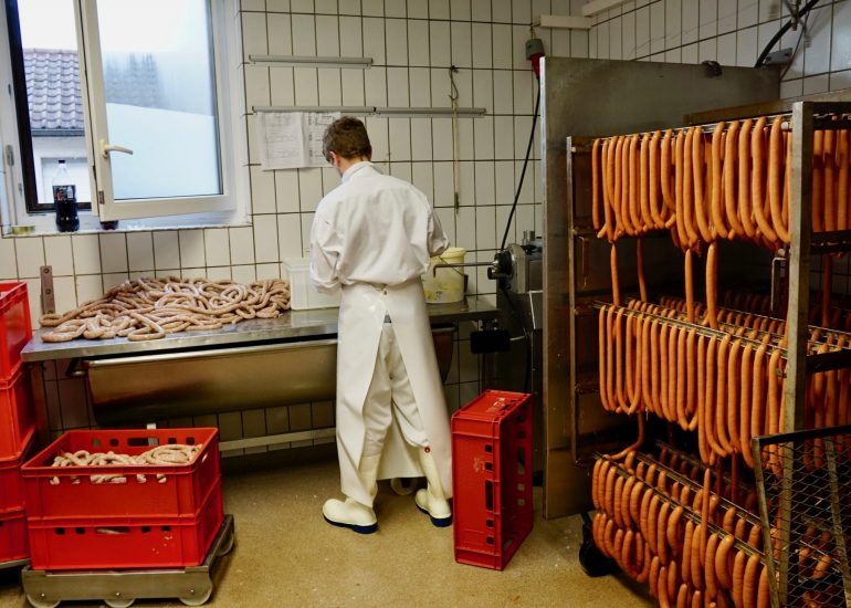 A man making sausages from behind and racks of Frankfurters