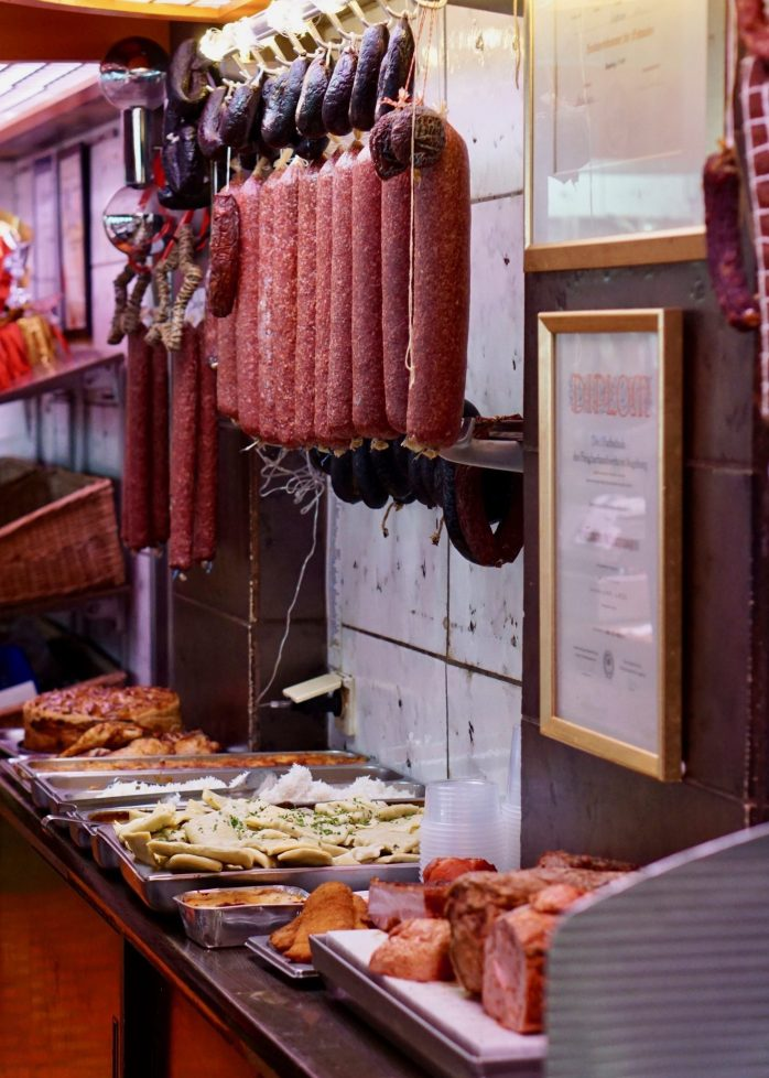 Hanging sausages and ready meals against a tiled wall