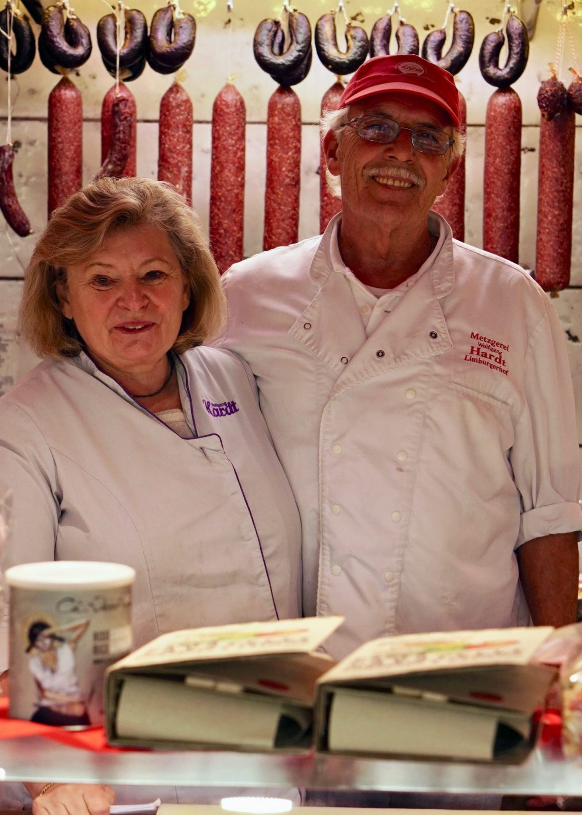 Anne-Marie and Wolfgang Hardt wearing white butcher's aprons behind their butcher's counter