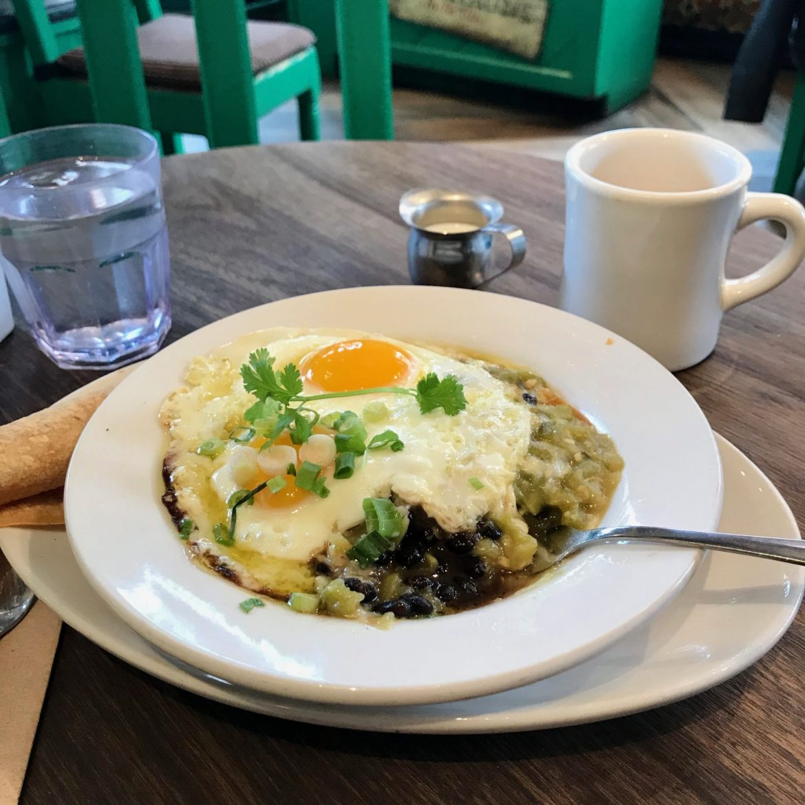 Huevos Rancheros with green chile in a white bowl
