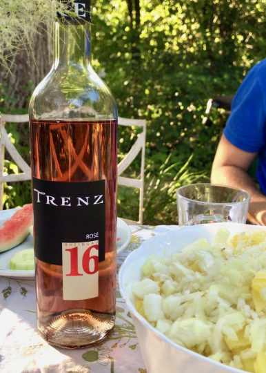 A nearly-full bottle of Trenz rosé wine on a table outdoors next to a bowl of potato salad