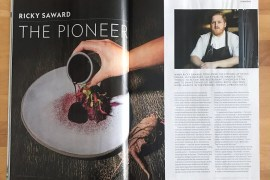 A copy of National Geographic Traveller Food UK open at a spread about chef Ricky Saward with pictures of food and Ricky and some text