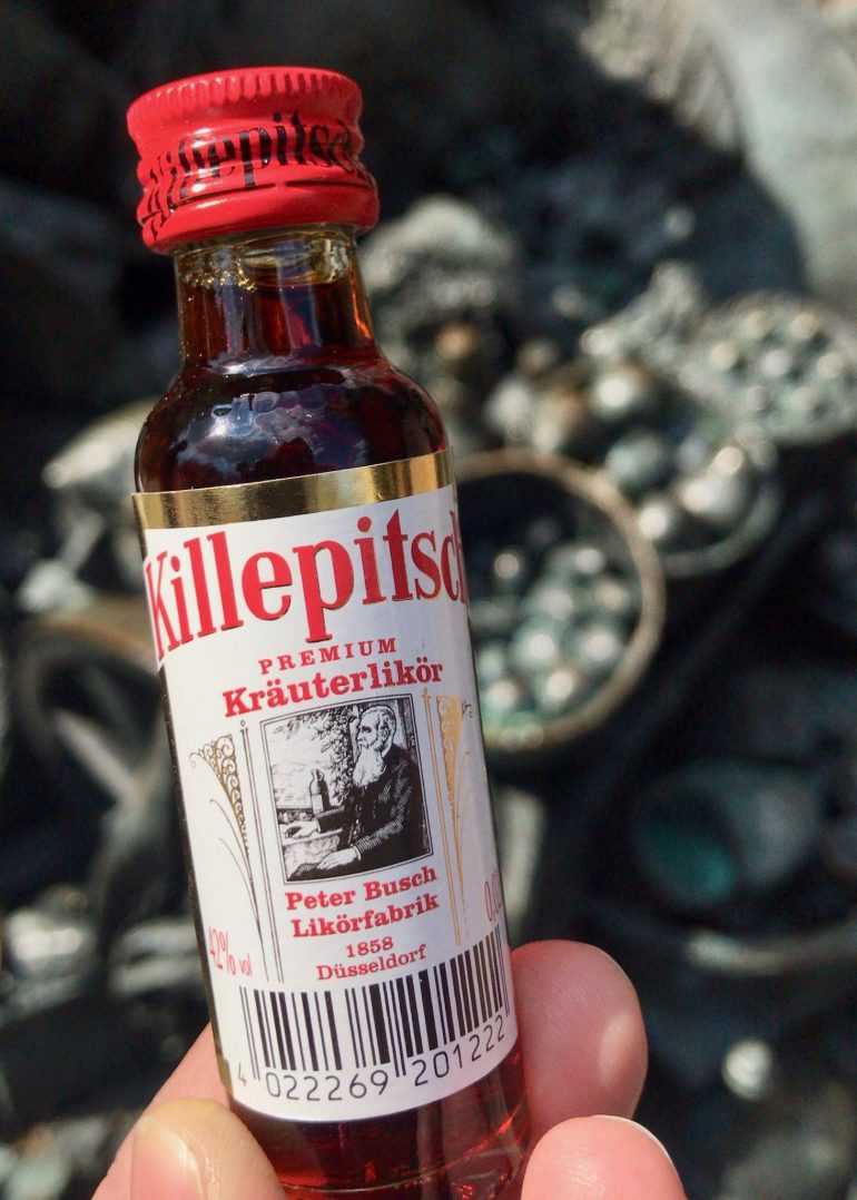 White fingers holding a tiny bottle of Killepitsch herb liqueur