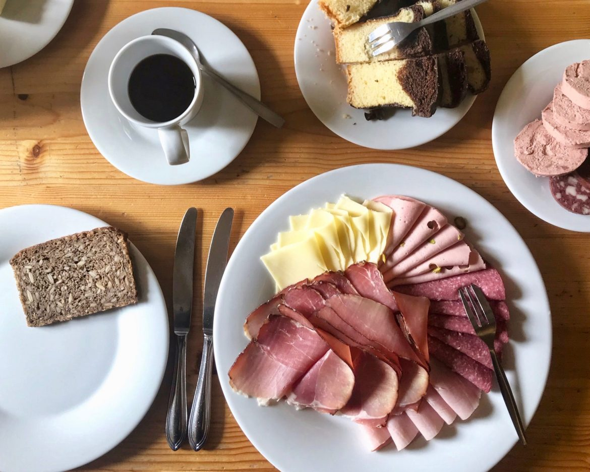 A spread of lunchmeatsa and cheeses, cakes and coffee cups on a wooden table