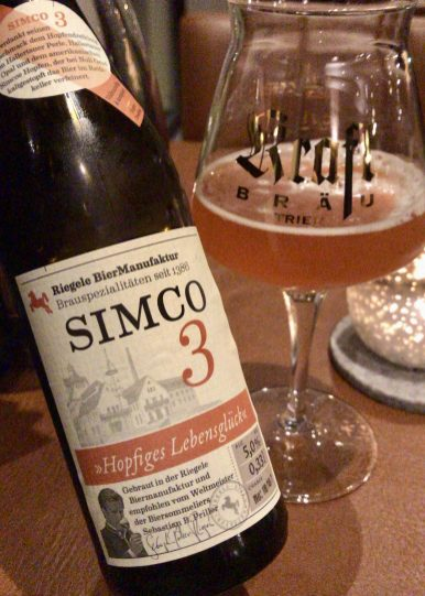 A bottle of Simco 3 beer next to a beer glass