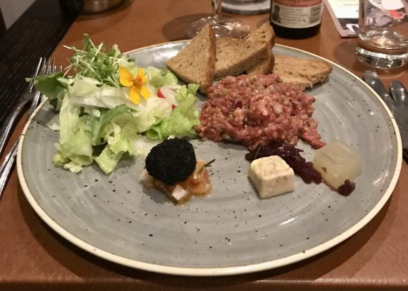 Beef tartare on a grey plate with various accompaniments