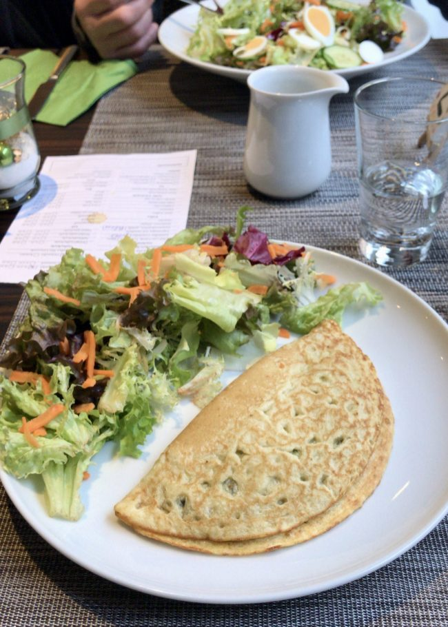 A folded pancake on a white plate with salad on the side