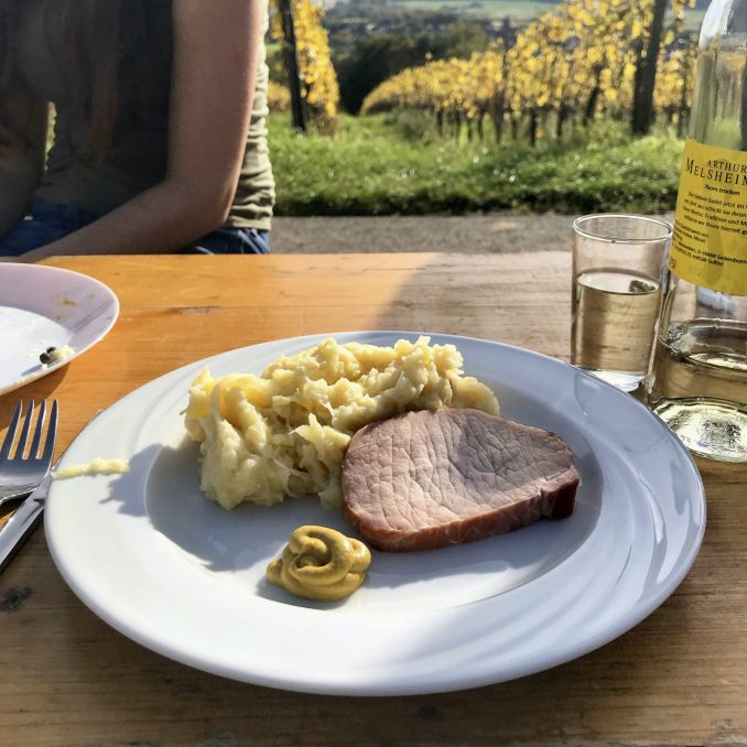 A cured pork steak with mashed potato and sauerkraut and a blob of mustard on a white plate on a trestle table in a vineyard