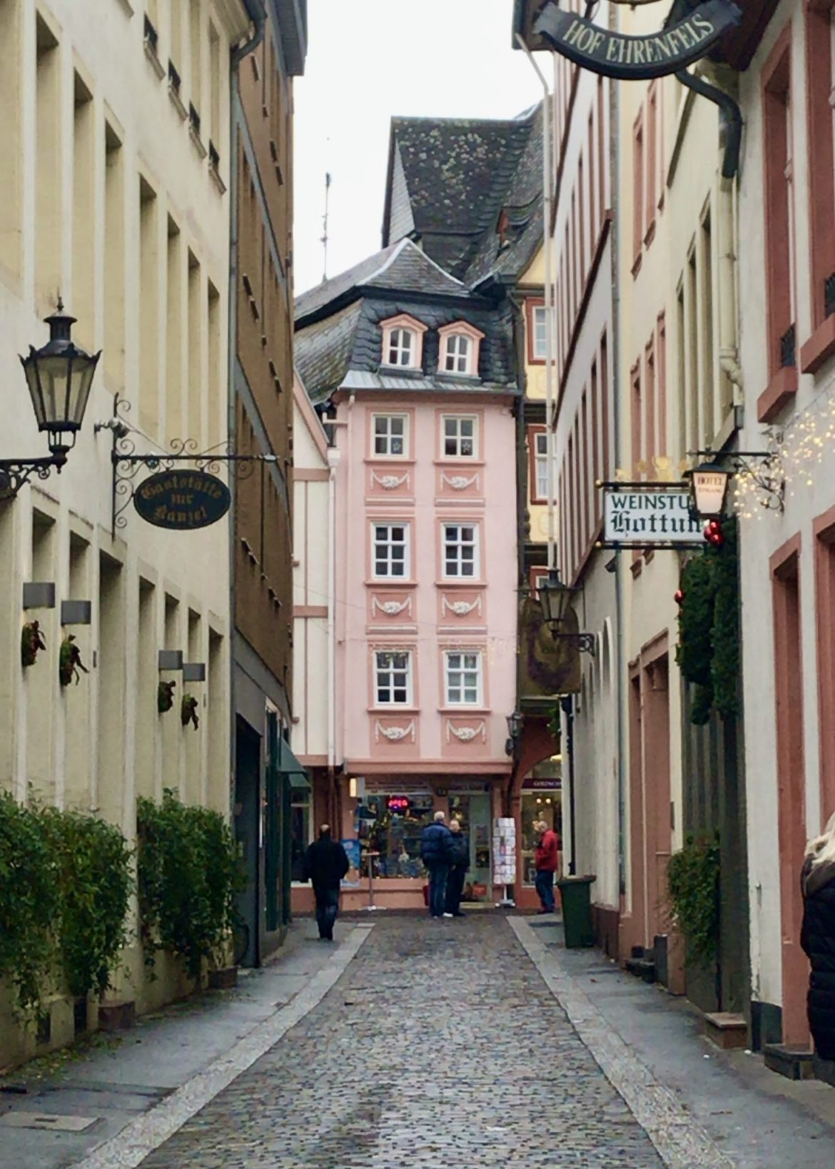 A very tall narrow pink house at the end of a cobbled street