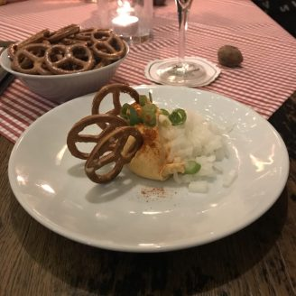 Spundekäse on a white plate with three pretzels on top