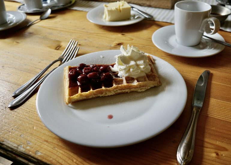 A rectangular waffle with whipped cream and sour cherries on top, all on a white plate with cutlery alongside