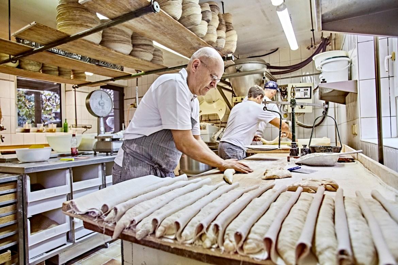 Baker Arnd Erbel rolling out bread dough in his workshop