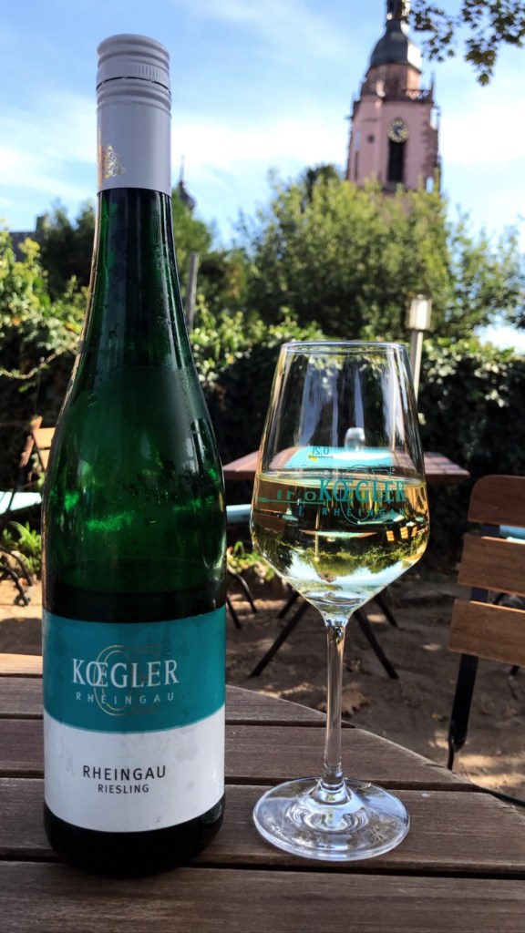 A bottle of Weingut J.Koegler Rheingau Riesling next to a glass of it on a table in a winery garden