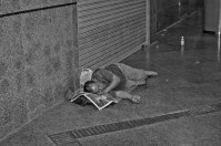A homeless man uses a newspaper as a pillow as he sleeps on the street in Singapore