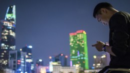 A man uses his phone in Ho Chi Minh city Vietnam at night