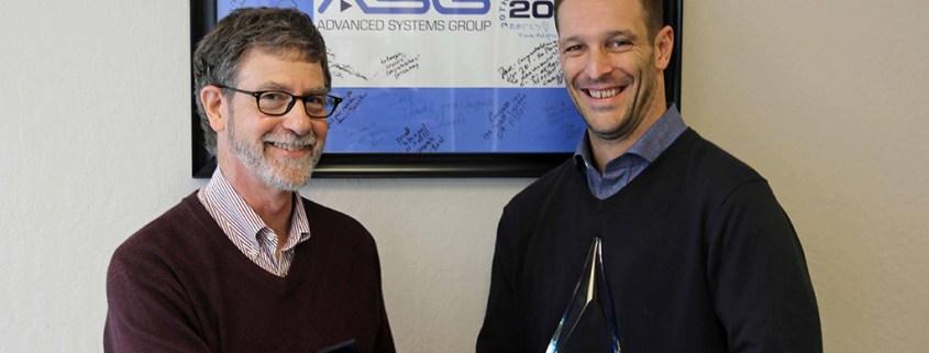 Primestream's Namdev Lisman (right) congratulates ASG's Dave Van Hoy for receiving the Platinum Partner Award.