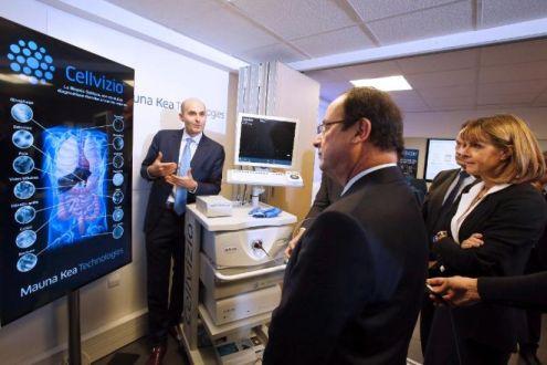 """François Hollande (c) et Anne Lauvergeon, présidente de la commission """"Innovation 2030"""", écoutent le PDG de Mauna Kea, Sacha Loiseau, qui leur présente le Cellvizio, le plus petit microscope flexible du monde, le 2 décembre 2013 à Paris (Photo François Mori. AFP)"""
