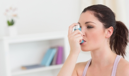 woman-using-asthma-inhaler-in-living-room