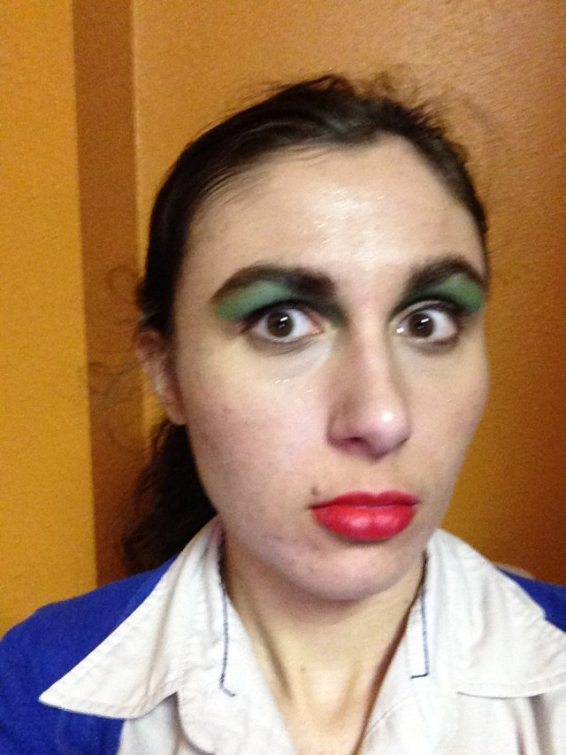 Ashlee Craft wearing a blue sweater, green eyeshadow, theatre makeup, a dress shirt, & ponytail