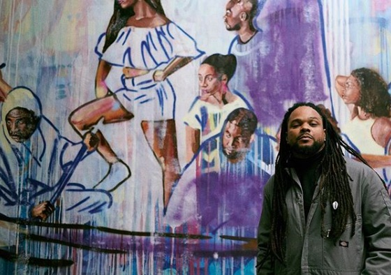 Bmike standing in front of one of his murals