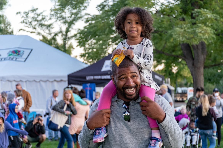Girl Sitting on Smiling Man's Shoulder