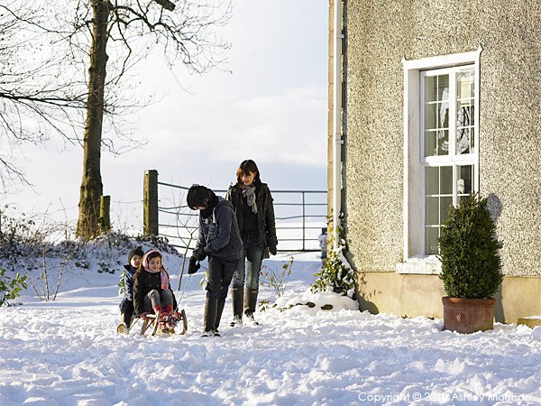 Nicola Nemec and her childern playing in the snow outside their farmhouse near Armoy in County Antrim.