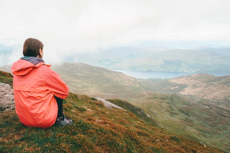 Girl sitting at the top of Ben Vorlich, Scotland