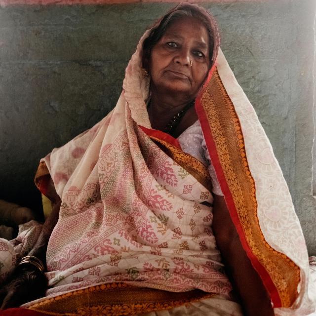 Saranga Devi siede sulla scalinata del fiume, accanto al fuoco sacro. È insolito, forse senza precedenti per una donna, l'essere a capo di una scalinata per le cremazioni. Ha ereditato il ruolo dal suo defunto marito, Dom Raja (foto di Andrea de Franciscis)