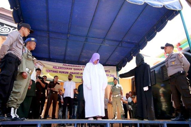 Remita Sinaga prima di ricevere 28 vergate sulla schiena. La donna e' stata condannata per aver venduto delle bevande alcoliche. Aceh, Indonesia, 11 aprile 2016. Foto AFP