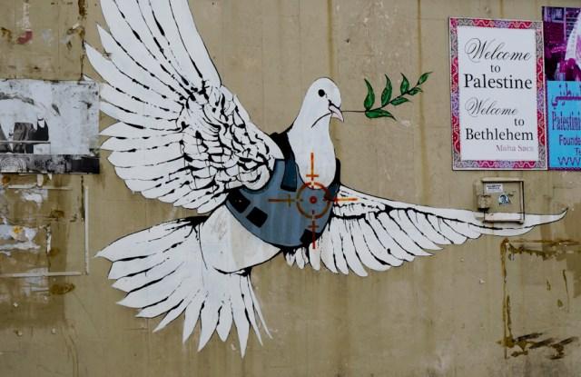 Un graffito dell'artista Banksy su un muro a Betlemme, Palestina.