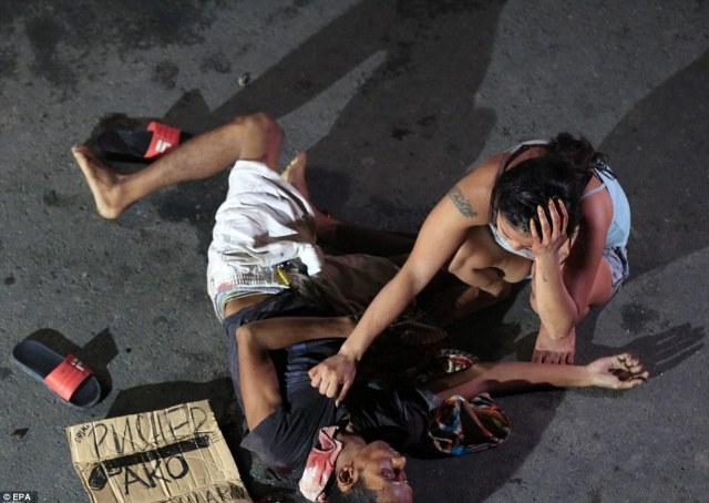 """Guerra alla droga nelle Filippine: una donna di fronte ad un uomo assassinato per strada a Pasay City, nela periferia di Manila. Vicino al cadavere si vede un cartello con la scritta """"pusher ako"""" (sono uno spacciatore) lasciato dagli assassini. Foto Getty"""