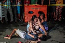 """Guerra alla droga nelle Filippine: due donne piangono di fronte ad un uomo assassinato per strada a Manila. Vicino al cadavere si intravede un cartello con la scritta """"pusher ako"""" (sono uno spacciatore) lasciato dagli assassini"""