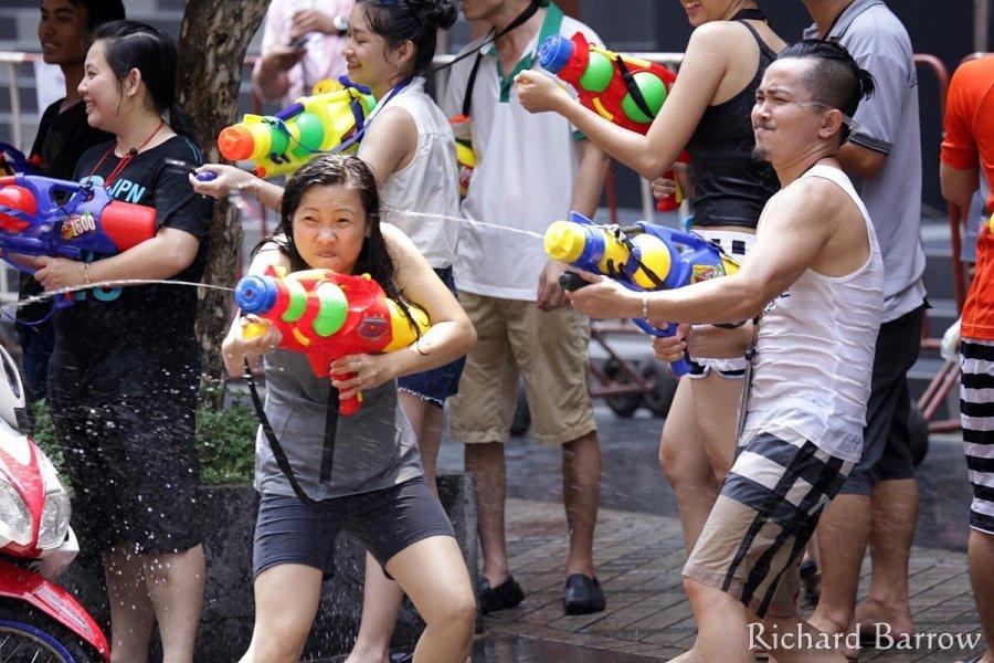 Giovani armati con pistole ad acqua partecipano alla battaglia di gavettoni davanti al centro commerciale Central World, Bangkok, Thailandia, aprile 2017. Foto Richard Barrow