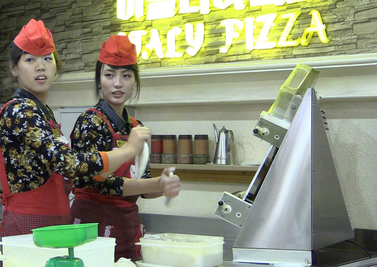 North Korean waitresses making dough style=