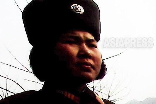 둥근 얼굴의 여병사가 시장으로 향하는 길을 터벅터벅 걷고 있다. 2011년 4월 평안남도에서 촬영 김동철(아시아프레스)