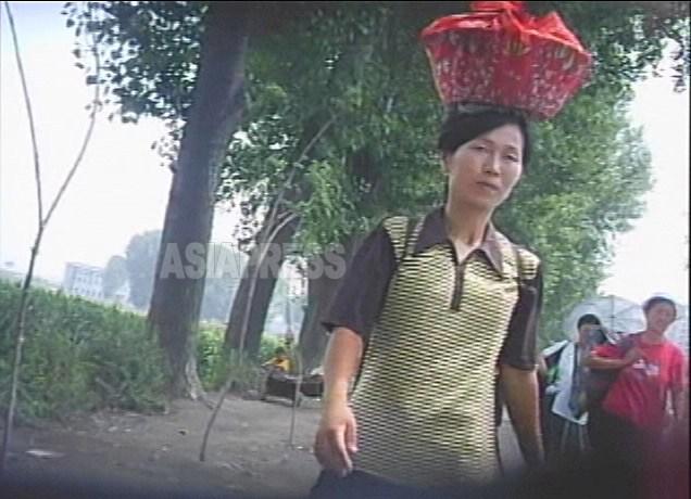 한국에서는 보기 드물어졌지만, 머리에 짐을 이고 나르는 것은 조선 여성의 습관이다. 시장으로 향하는 길을 걷는 여성. 2007년 8월 평양시 력포구역에서 촬영 리준(아시아프레스)